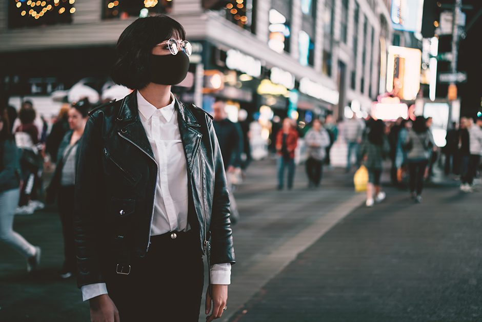 Stylish hipster girl dressed in trendy jacket walking outdoors on avenue of metropolis with crowd of people.Brunette young woman in eyeglasses looking away standing on New York street et evening